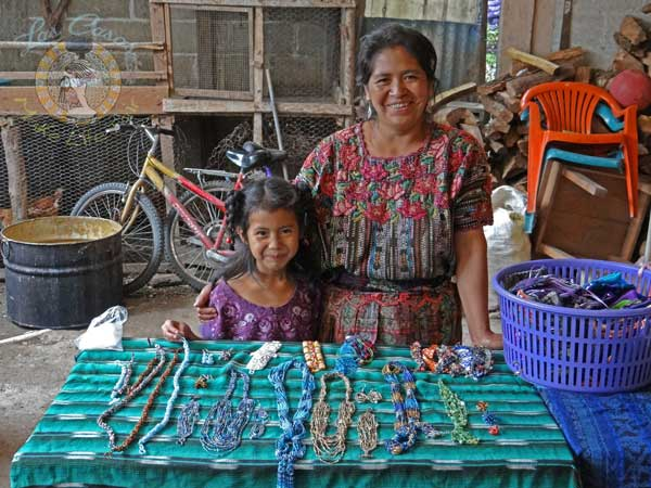 Guatemalan artisan with table of jewelry