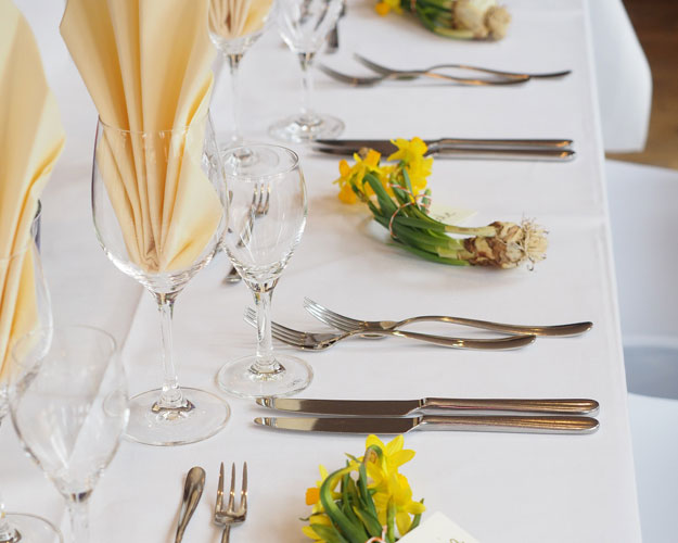 Elegant table setting with white linens and daffodils