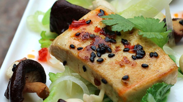 Fancy tofu appetizer on greens with mushrooms
