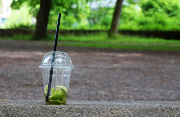 Empty plastic smoothie cup sitting on pavement in park