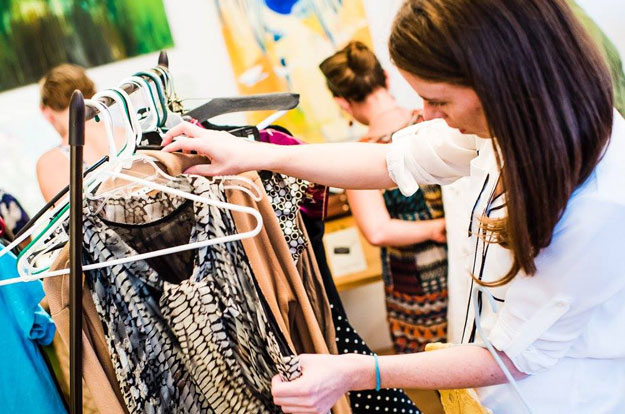 Woman browsing dresses at clothing swap