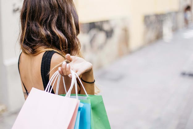 Woman holding three shopping bags over her shoulder